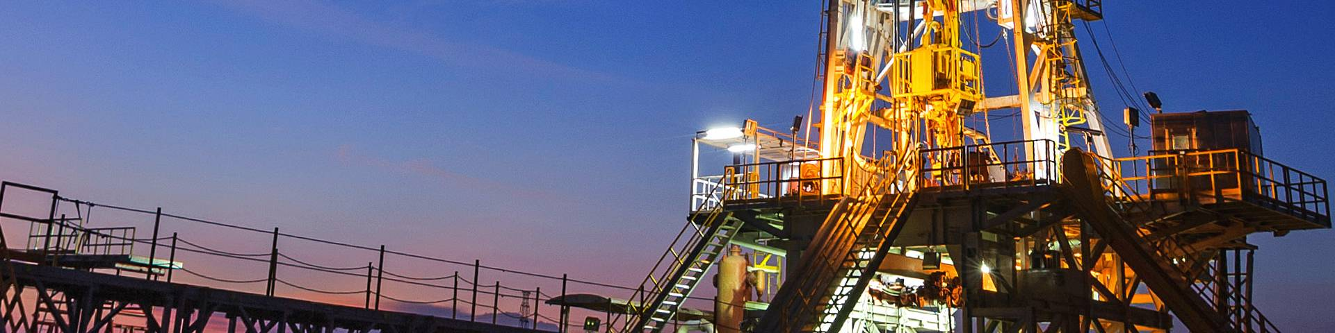 A brightly lit oil drilling rig looks very majestic.